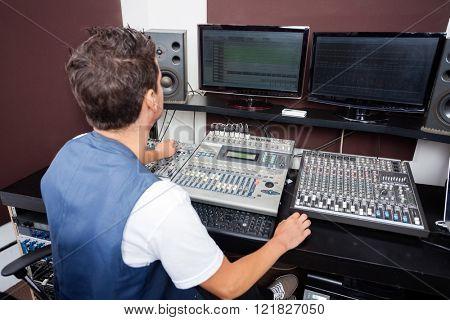 Man Mixing Audio In Recording Studio