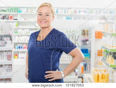 Female Pharmacist Standing With Hands On Hip In Pharmacy