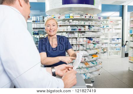 Happy Chemist Explaining Details Of Product To Customer