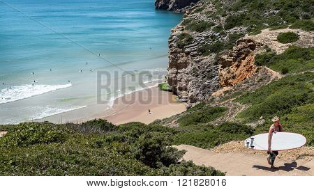 Beliche beach in the Algarve with people surfing.