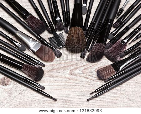 Makeup Brushes Arranged In Semicircle On Shabby Wooden Surface