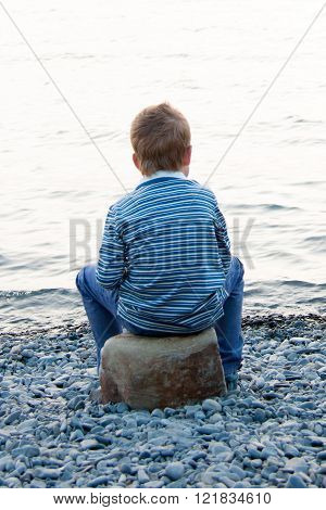 Boy Sitting Near Water