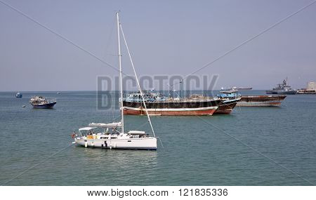 GULF OF ADEN, REPUBLIC OF DJIBOUTI FEBRUARY 08, 2016: Luxury sailing boat, fishing, cargo and warships at anchor in the port of Djibouti