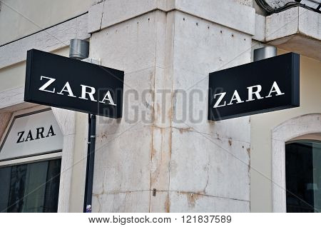 LISBON PORTUGAL - DECEMBER 25: Zara store sign on the grey building on Agusta street in Baixa district of Lisbon on December 25 2012. Lisbon is the largest city and capital of Portugal with a population of 547 000 citizens.