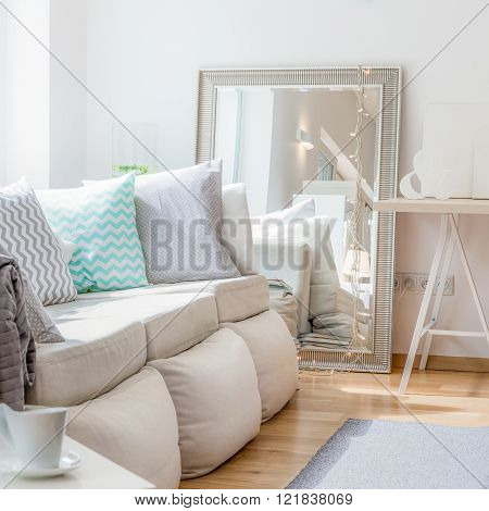 Photo of comfortable large sofa with decorative cushions
