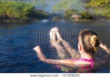 Young woman relax in a hot spring. Iceland Landmannalaugar