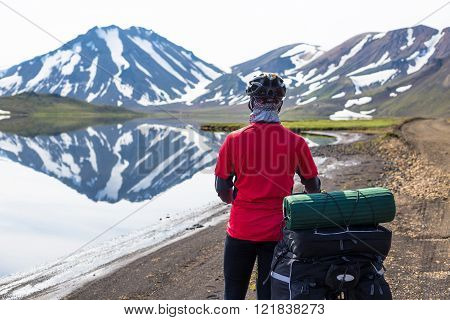 Happy biker on backdrop of lake and snowing mountains in Iceland