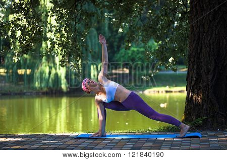 Young woman doing yoga in beautiful morning near lake