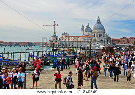 VENICE ITALY - SEPTEMBER 28: Tourists goes down the street in historical centre of Venice on September 28 2012. Venice is a city in northeastern Italy sited on a group of 118 small islands.