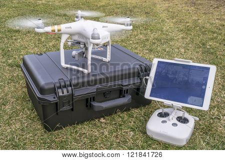 Fort Collins, CO, USA - March 12, 2016:  DJI Phantom 3 quadcopter drone is taking off from a pelican case with radio controler and iPad in foreground