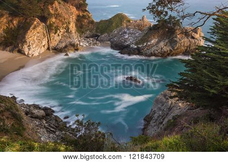 Waterfall in Julia Pfeifer Burns State Park at sunset with a soft golden color on the rocks