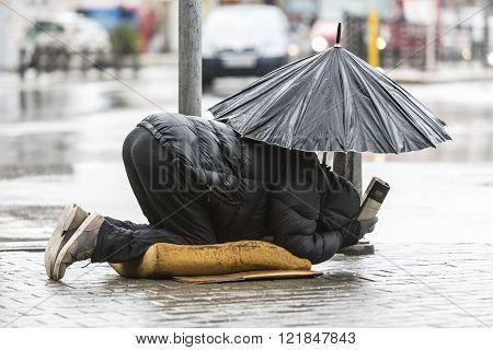 Homeless beggar with umbrella in the rain