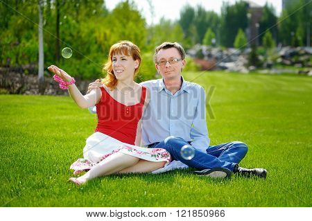 couple love sitting on green grass in summer meadow