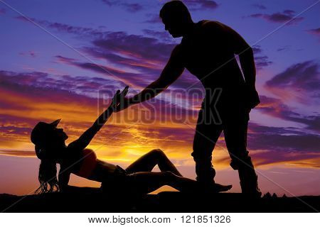 A silhouette of a cowgirl reaching up to grab onto her man's hand.