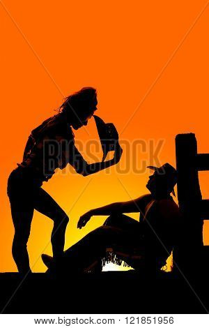A silhouette of a cowgirl bending over the top of her cowgirl.