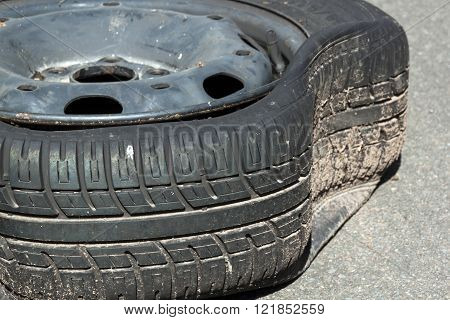 Closeup Of Dirty Damaged Deflated Tire After Blowout