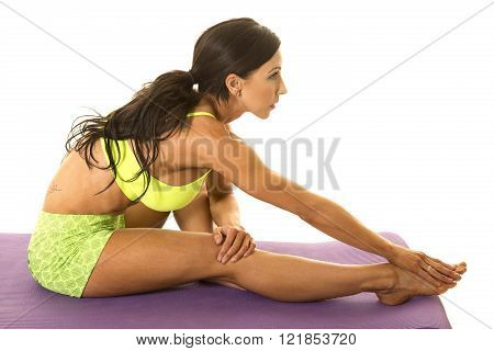 a woman sitting on her fitness mat reaching and stretching out her body.