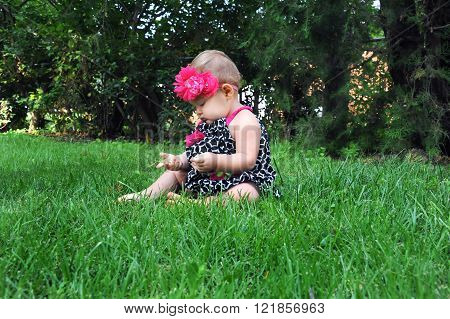 Baby girl holds blade of grass and examines it. She is sitting in the grass with barefeet.