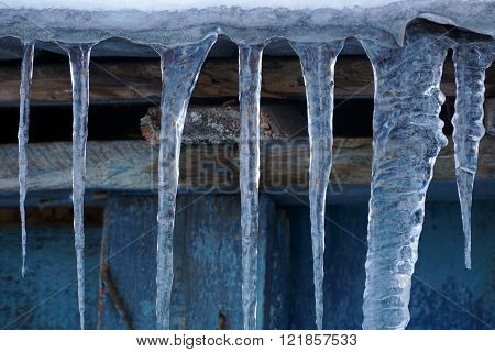 many icicles hanging on the wooden roof