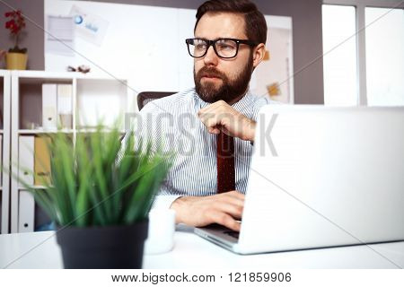 Confident young man working on laptop while sitting at his working place in office