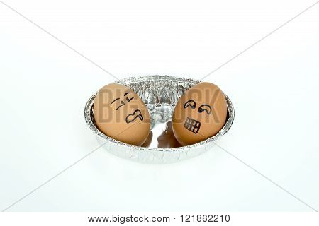 Two Eggs With Funny Faces On Oval Foil Tray, Isolated On White Background