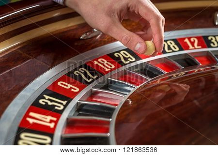 Roulette wheel and croupier hand with white ball in casino