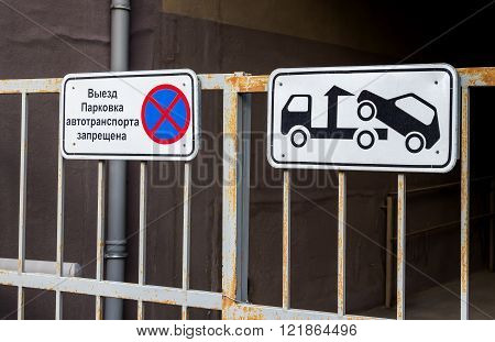 Traffic sign prohibiting parking mounted on metal gate. Evacuation on tow truck. Text in Russian:
