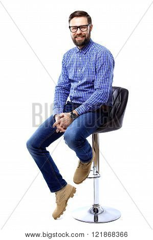Proud and satisfied young man sitting on chair and looking at camera isolated on white