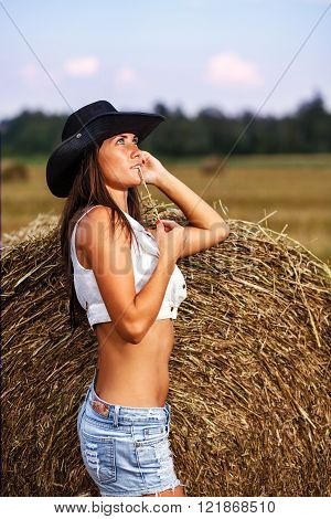 Girl in cowboy hat and jeans shorts with straw