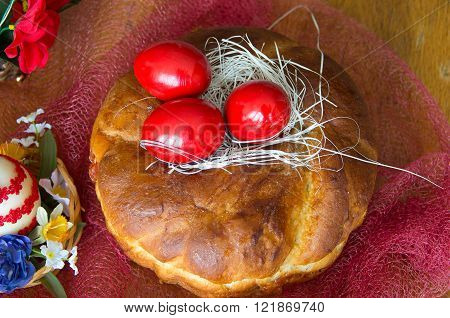 Red wooden Easter eggs on the loaf.