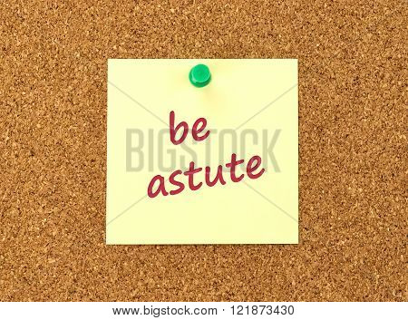 The phrase Be Astute in red text on a yellow sticky note posted to a cork notice board.
