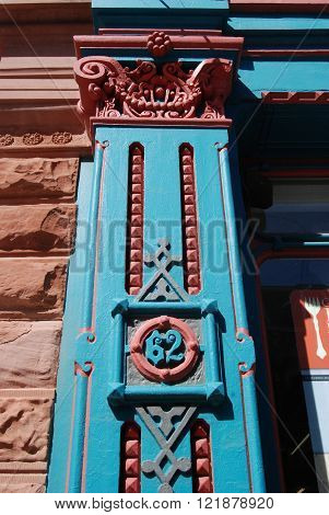 A late 1800s architectural feature column, painted in blue and copper.