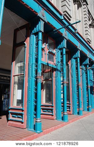 Blue and copper painted metal columns and storm doors along an 1800s sidewalk storefront.