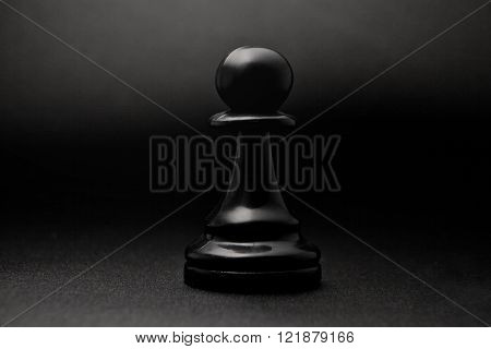 Chess. Black pawn on a black background. Pawn, infantry chess.