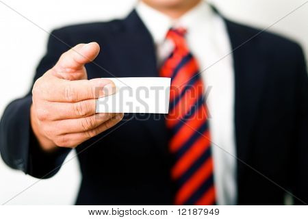 Businessman presenting his (blank) business card (shallow depth of field)