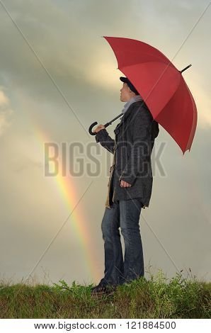 Woman with umbrella outdoors in rainy weather with rainbow