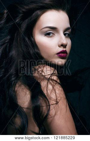 beauty young brunette woman with curly flying hair, femme fatal on black background, low key, stylish concept