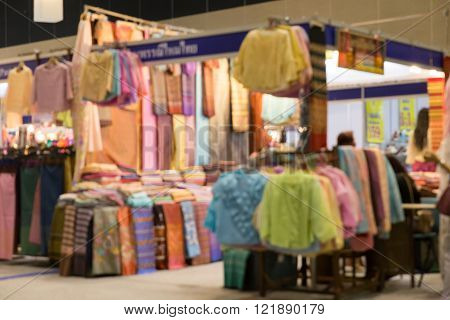 colorful woman cloth apparel selling in shop at tradeshow fair (blur background)