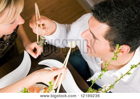 Couple feeding each other with sushi for dinner, romantic setting, presumably this is an advanced date; shallow focus on eyes