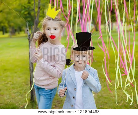 little boy and girl posing with paper masks on a cheerful children's holiday.