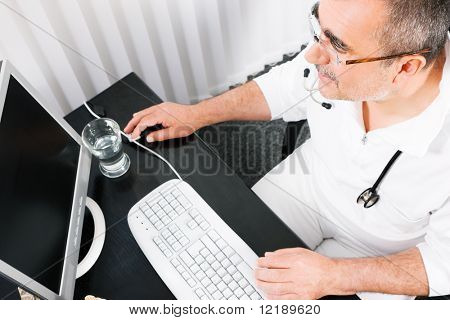 Medical doctor doing some office stuff using his computer (focus on eyes)