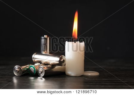 Blackout concept. Few batteries near lighting candle on dark background