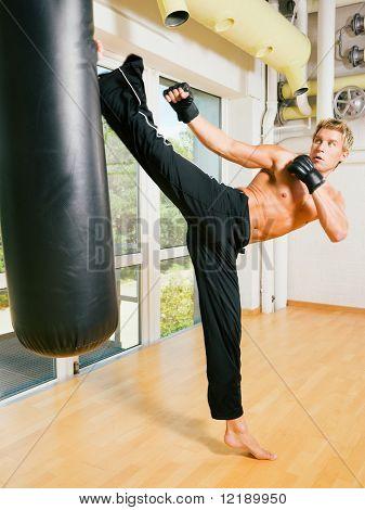 Man training his martial art skills kicking the sandbag aggressively
