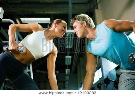 Paar in der Turnhalle, rivalisierenden einander, Training mit Hanteln (Fokus auf die Gesichter)