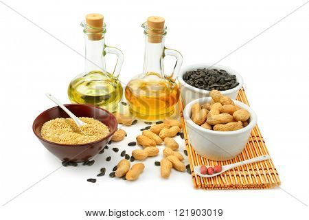 Sunflower seeds, peanuts and oil isolated on white