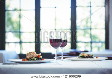 Squid ink spaghetti dish with basil for two with glasses of red wine in a restaurant
