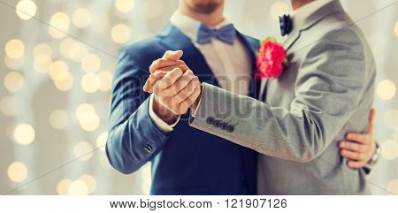 people, homosexuality, same-sex marriage and love concept - close up of happy male gay couple holding hands and dancing on wedding over holidays lights background