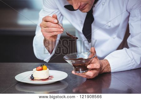 Chef putting chocolate sauce on a dessert in a commercial kitchen poster