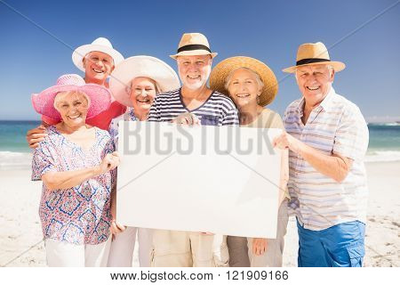 Smiling senior friends holding blank paper on the beach