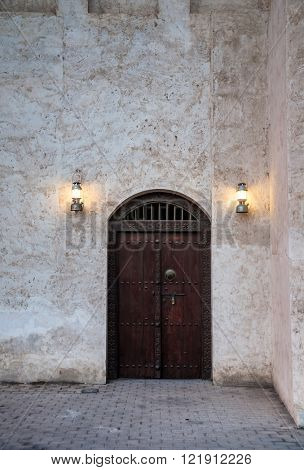 An old door with illuminated hanging lamps.